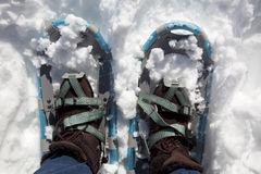Woman with boots and snowshoes. View downward at woman in snow boots and snowshoes in the snow Royalty Free Stock Images
