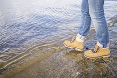 Woman in boots takes a step into the water from a flooded river. Pier, warm spring day stock photo