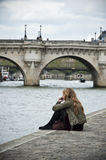 Woman in border Seine river near new bridge (pont neuf) Royalty Free Stock Image