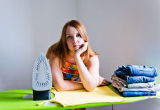 Woman bored of doing the ironing. Royalty Free Stock Images