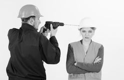 Woman with bored face in helmet ignoring husband annoying her. Man with drill tool drills head of woman, white background. Builder, repairman makes hole in stock photos
