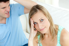 Woman bored by her boyfriend getting worked up. Both on the sofa Stock Photography