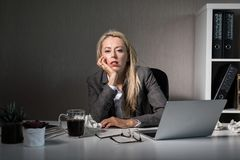 Woman bored at her job. Middle aged business woman bored at her job royalty free stock image