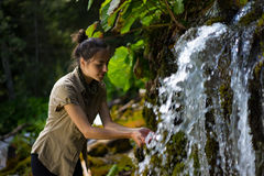 Woman with both hands at the waterfall Stock Photo