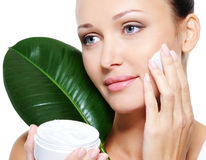 Woman with a bottle of cosmetic cream Stock Images