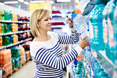 Woman with bottle drinking water in shop Stock Images