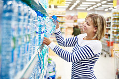 Woman with bottle drinking water in shop Royalty Free Stock Photography