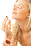 Woman with bottle of perfume. Portrait of young beauty woman smelling perfume with closed eyes, on white background Stock Photo
