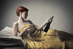Woman with a bottle of sparkling wine. Woman into bed with two glasses and a bottle of sparkling wine royalty free stock image