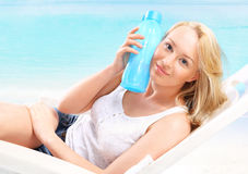 Woman with bottle of water on beach Royalty Free Stock Photo
