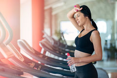 Woman with bottle of water exercising on treadmill in gym Royalty Free Stock Photography
