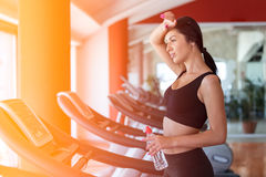Woman with bottle of water exercising on treadmill in gym Royalty Free Stock Images