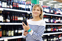 Woman with bottle of wine in store Stock Photos