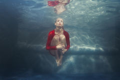 Woman on the bottom of the pool wearing a dress. Woman at the bottom of the pool dressed in a red dress Royalty Free Stock Images