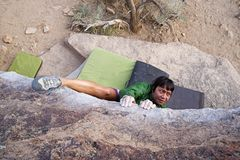 Woman Bouldering From Above. A woman bouldering on a traverse from above with a heel hook Stock Photo