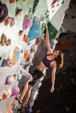 Woman bouldering in climbing gym Royalty Free Stock Photography