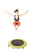 Woman bouncing on trampoline Stock Photos
