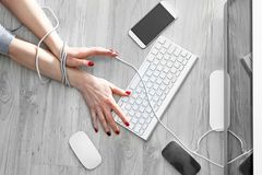 Compulsive computer use, a slave to new technologies. A woman with bound hands writes on a computer keyboard stock image