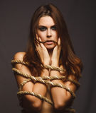 Woman bound rope prisoner in jeans Stock Photo