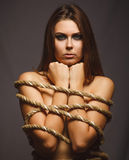 Woman bound rope prisoner in jeans gray background Royalty Free Stock Image