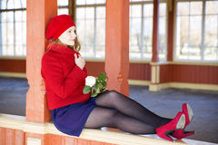 Woman on boundaries adjust red coat collar. Resting woman on boundaries adjust red coat collar Stock Images