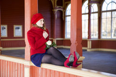 Woman on boundaries adjust red coat collar Stock Photo