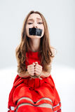 Woman bounded using ropes sitting with closed mouth by tape Stock Image