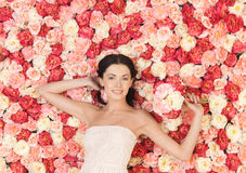 Woman with bouquet and background full of roses Stock Image