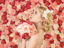 Woman with bouquet and background full of roses Royalty Free Stock Image