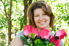 Woman with a bouquet of flowers in summer park Stock Photography