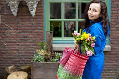 Woman with a bouquet of fresh tulips yellow and pink in the hands. With corset for shopping. On the street of the old European. City. Blooming flowers. Buying royalty free stock images