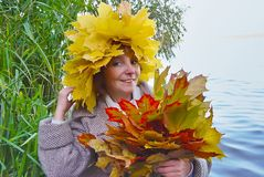 Woman with bouquet maple autumn leaves. Cheerful woman with bouquet maple autumn leaves on background of the river Royalty Free Stock Photos