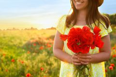 Woman with bouquet of poppies in field on sunny day. Space for text stock images