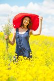 Woman with a bouquet in a red hat on a sunny day amidst wildflow Stock Photos