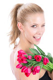 Woman  bouquet of red tulips flowers wink Royalty Free Stock Photos