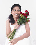 Woman with a bouquet of roses. Woman sitting with a bouquet of roses royalty free stock photography