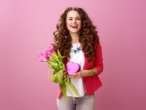 Woman with a bouquet of tulips and a heart shaped box of chocola. Pink Mood. Portrait of happy stylish woman with long wavy brunette hair isolated on pink Royalty Free Stock Photo
