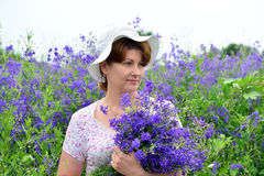 Woman with a bouquet of wild flowers on the lawn. Woman with a bouquet of a wild flowers on the lawn stock photos
