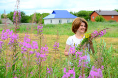 Woman with bouquet of wildflowers on the background of village Stock Photos