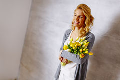 Woman with a bouquet of yellow tulips by the wall Royalty Free Stock Images
