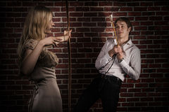 Woman with bow and arrow hunting a man. Gorgeous blond hair women wearing elegant dress hunting a man. Her arrow hits the center of his heart. Red brick wall Stock Images