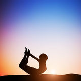 Woman in bow yoga pose meditating at sunset. Zen Royalty Free Stock Images