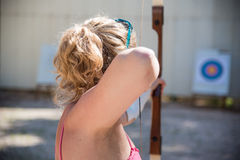 Woman with a bow. Young woman aiming with a bow Royalty Free Stock Images