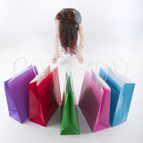 Woman Bowing on Floor In Front of Shopping Bags Royalty Free Stock Images