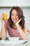 Woman with a bowl of cereals, orange juice and newspaper in kitchen Stock Images