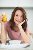 Woman with a bowl of cereals, orange juice and newspaper in kitchen Royalty Free Stock Photos