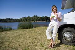 Woman with bowl by motor home and lake, smiling, portrait, low angle view Stock Images