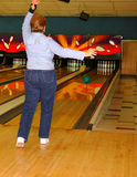 Woman bowler in action. Senior woman bowler releasing her ball in hopes of a strike Stock Photo