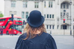 Woman in bowler hat and graduation gown Stock Photo