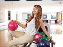 Woman With Bowling Ball Sitting On Rack Royalty Free Stock Image